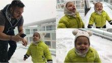 Коцето куфее на снега със сина си